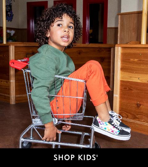 Kid in Go toping cart wearing Vans sneakers