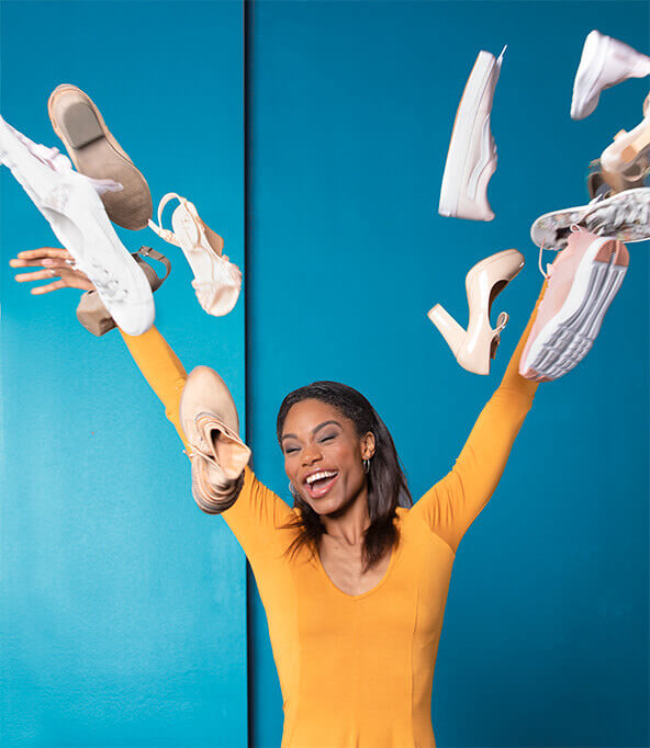 a happy woman throwing shoes in the air