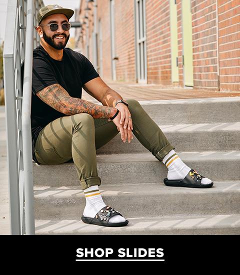 Man wearing Crocs slide sandals